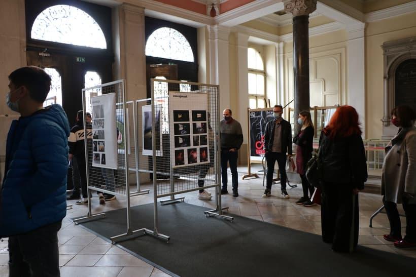 Skupina obiskovalcev v avli šole na otvoritvi razstave Fotografija v sodobnih kontekstih